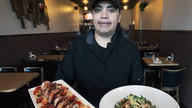 Chef Valerie Estala with two of her dishes from Fuzion Casual Fine Dining at 12380 Edgemere. At left is Stuffed Bacon Wrapped Shrimp and Chicken Piccata is at right.