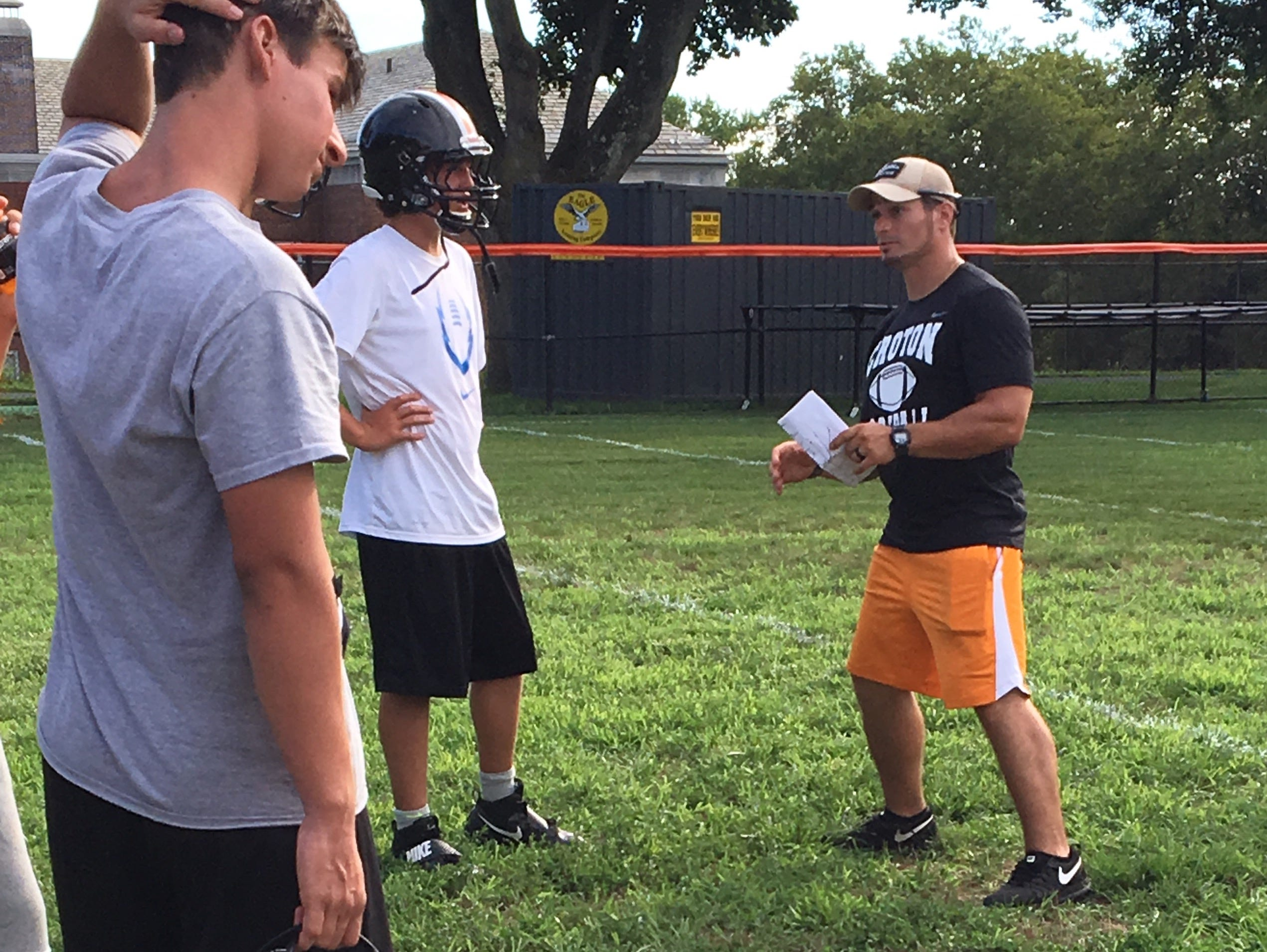 First-year coach Joe Streany talks to quarterback Toby Murphy during the first day of football practice at Croton-Harmon High School on Aug. 15, 2016.