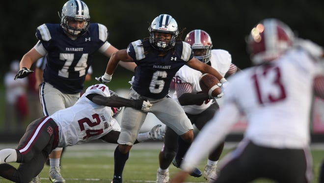 Farragut's Isaiah Gibbs (6) evades a tackle by Oak Ridge's Adarius Simpson (24) during a high school football game at Farragut against Oak Ridge, Friday, Sept. 8, 2017.