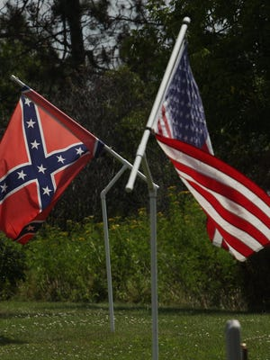 American and Confederate flags fly near the driveway of a residence along Highway 10 west of Marshfield, Wednesday, July 22.