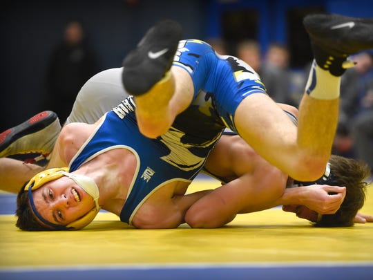 Northern Lebanon's wrestler Zach Kelly, battles Anthony Rini of Camp HIll at 138 pounds on Wednesday in the District Three Class AA team tournament opener.