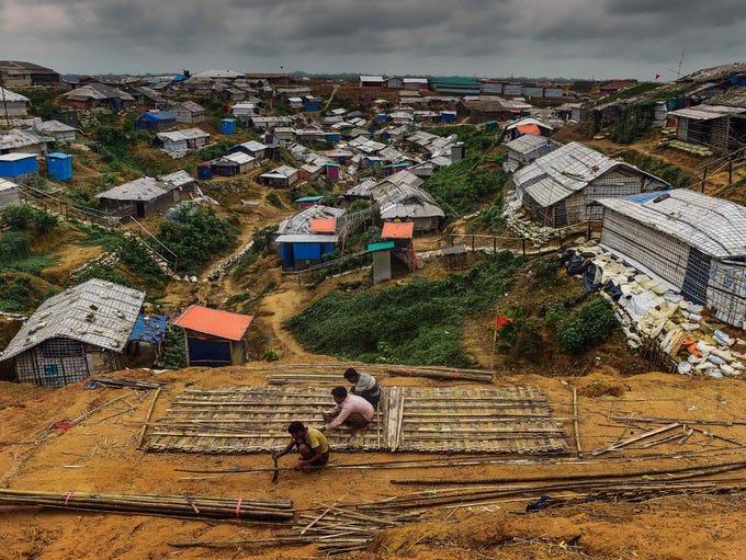 Rohingya refugees use bamboo to build a shelter at