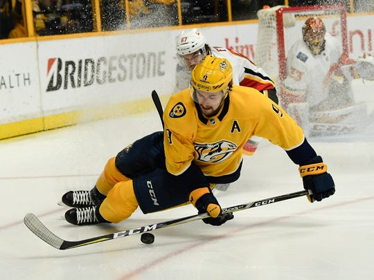 Predators forward Filip Forsberg takes the puck from Flames forward Michael Frolik during a February game.