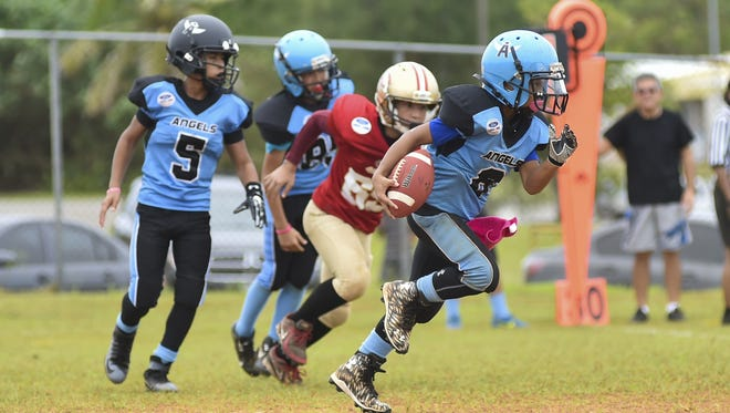 Marcus Camacho (8) of the Windward Hills Memorial Park Hal's Angels runs the ball for the touchdown against the PXC Southside 49ers during their Triple J Ford GNYFF Youth Football League game at Hal Shiroma Field in Dededo on Sept. 19.