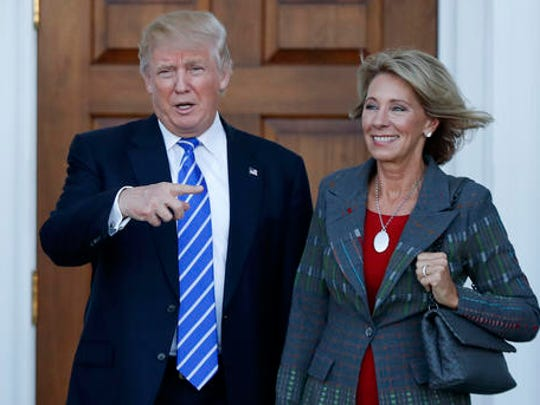 FILE - In this Nov. 19, 2016 file photo, President-elect Donald Trump and Betsy DeVos pose for photographs at Trump National Golf Club Bedminster clubhouse in Bedminster, N.J. Trump chose charter school advocate DeVos as education secretary in his administration, and she was confirmed last week.