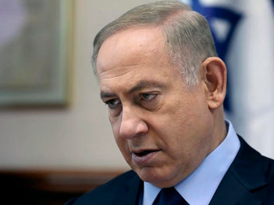 FILE - In this Sunday, Jan. 1, 2017, file photo, Israeli Prime Minister Benjamin Netanyahu chairs a weekly cabinet meeting, in Jerusalem. Israel's Benjamin Netanyahu should be upbeat these days: The economy is growing, his opposition is weak and the incoming Trump Administration seems friendly, even to the much-maligned Jewish settlements in the West Bank. Instead, the long-serving leader is mired in a series of eye-popping corruption investigations in a country that has already jailed a prime minister and president.