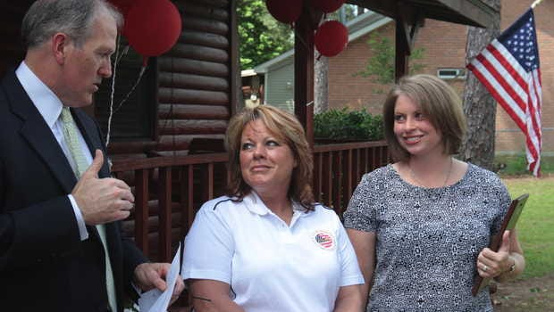 Ted Longo, left, and Elizabeth Sones of Merrill Lynch, right, present Army veteran Julie Barcheers with the keys of a house in Carriere on Thursday, May 8, 2014. Merrill Lynch supports the Military Warriors Support Foundation which provided the house.