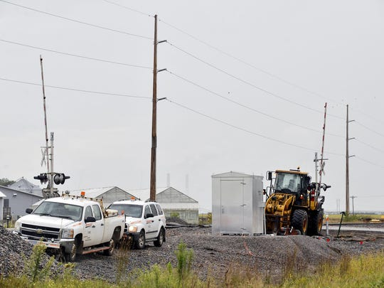 A crew works along the BNSF Railway crossing at Sherburne County Road 11 east of Becker on Wednesday. BNSF is adding a double railroad track between Becker and Big Lake and near Little Falls as part of its nationwide expansion effort.