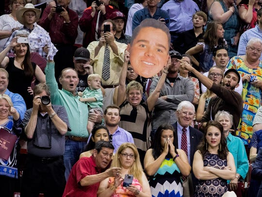 The giant head cutout of graduate Conrad Martinez proudly lifted by his family members in support of his accomplishments at the 2016 NMSU graduation ceremony.