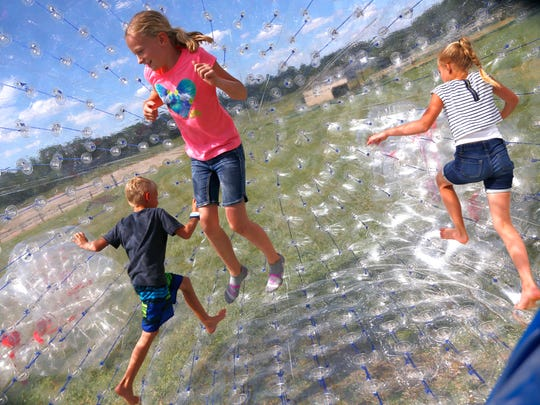 Maddox Jones, 7; Tenley Munson, 10; and Elle Jones, 8, play around in a Zorb at the Clear Fork Adventure Resort in Butler. The resort is on the sight of a former skiing resort and will have its grand opening this Saturday.