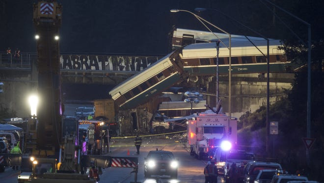 Work crews prepare to clear southbound Interstate-5 lanes at the scene of an Amtrak train derailment in DuPont, Wash.