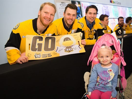 Mississippi RiverKings' Steven Hoshaw, Matt Harington and Sam Higgins smile for a photo with a child at St. Jude during the RiverKings visit last week.