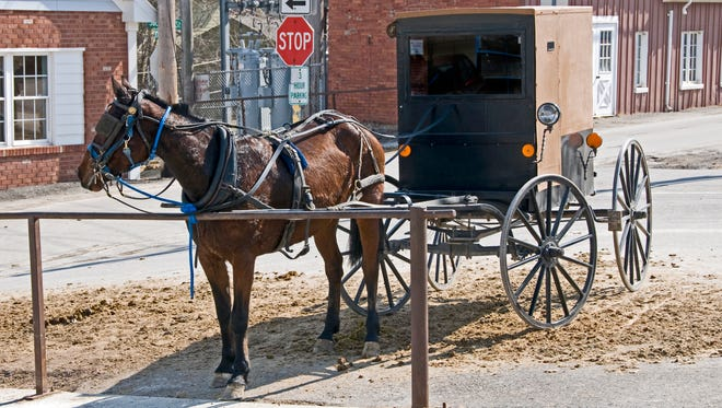 Amish horse and buggy hitched to a post in a modern community