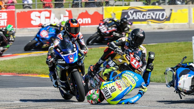 Cameron Beaubier (1) and Matthew Scholtz (11) try to dodge a tumbling Jake Lewis during a multiple-rider crash in Turn 5 during the Superbike feature.