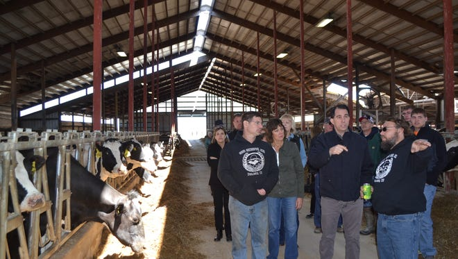 Mike Sievert, front right, and Gov. Scott Walker on April 25, discuss the damage to the dairy barn he and his brother Rod Sievert, front left, operate near Sobieski. Walker and state Secretary of Agriculture Sheila Harsdorf (at Walker's right) along with state FSA executive Sandy Chalmers stopped at two farms to hear from dairy operators in person.