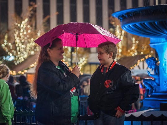 Stephanie and Ashton Brown stand under their umbrella during the drizzle on Fountain Square Friday evening. Hundreds made their way to Fountain Square November 27, 2015 to watch the Macy's Light Up the Square event.