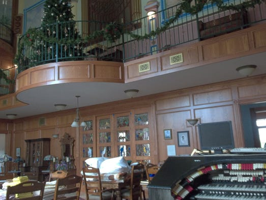 A great room includes wood paneling, a pipe organ and