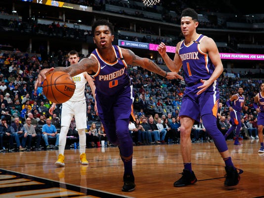 Phoenix Suns forward Marquese Chriss, front left, reaches out to pull in a loose ball as guard Devin Booker, front right, and Denver Nuggets center Nikola Jokic, of Serbia, look on in the first half of an NBA basketball game Wednesday, Jan. 3, 2018, in Denver. (AP Photo/David Zalubowski)