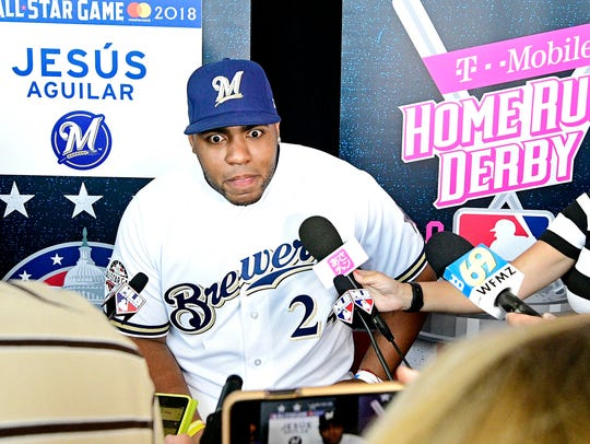 Jesus Aguilar of the Milwaukee Brewers (24) talks to