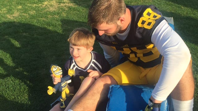 Jake Butt visits with 10-year-old Jesse Baker of  Titusville, Fla., during Michigan's practice Tuesday.