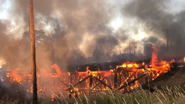 A railroad trestle burns in a grass fire in north Salem Friday morning.