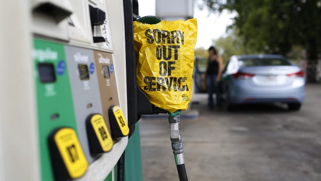 "A ""Sorry out of Service"" sign is placed on one of the gas pumps at a gas station."