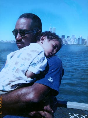 Adrian Padilla held by his father, Donald Padilla, with the World Trade Center in the background.