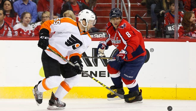 Apr 14, 2016; Washington, DC, USA; Philadelphia Flyers defenseman Nick Schultz (55) and Washington Capitals left wing Alex Ovechkin (8) chase the puck in the first period in game one of the first round of the 2016 Stanley Cup Playoffs at Verizon Center. Mandatory Credit: Geoff Burke-USA TODAY Sports
