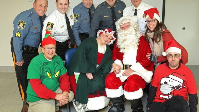 Officers from the Morris County Sheriff's Department and Park Police stopped by Zufall Health Center in Dover to drop off presents gathered during their recent toy drive. The drive was organized by Undersheriff William Schievella (back row, right), who recruited his parents, Daniel and Marylin, to play Santa and Mrs. Claus. Others in the photo are, standing from left, Sgt. Robert Franz, Chief Gabe DiPietro, and Lt. Steven Ferraioli of the Morris County Park Police, Undersheriff Michael Puzio and Schievella. Flanking Santa from left: Zufall helpers James Mastrangelo, Special Populations Director Michelle Blanchfield, and Shane Mastrangelo.
