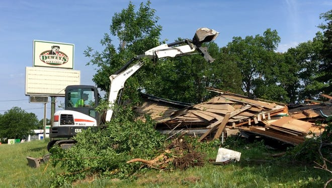 Passing motorists honked, waved and gave a thumbs-up as the long-abandoned Dewey's Bar & Grill, on the northeast corner of M-36 and Chilson Road in Hamburg Township, was demolished Saturday.