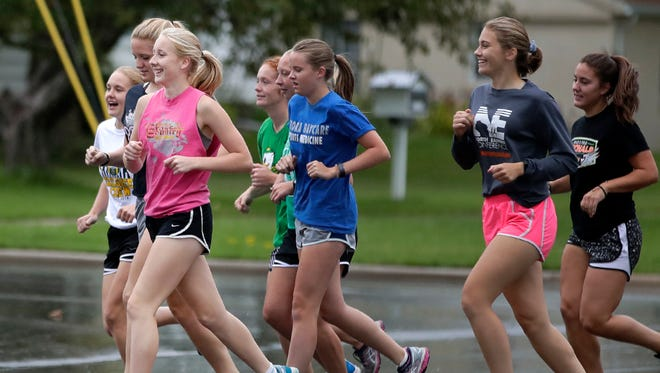 Jaci Hinz (left, in pink) runs with other members of the Freedom girls cross country team during practice this season.