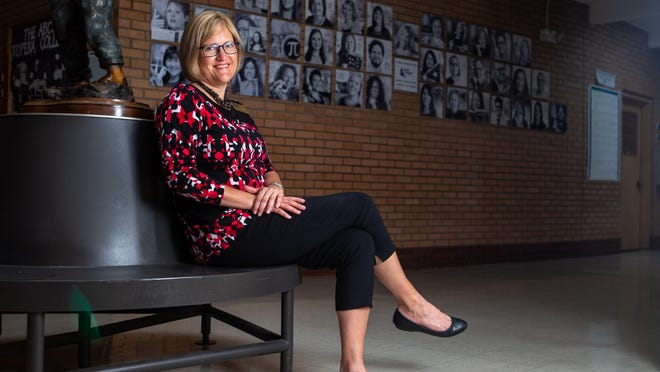 Topeka Collegiate School principal Lyn Rantz sits on a bench in front of staff portraits inside the school.