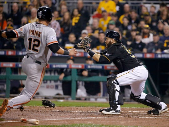 San Francisco Giants' Joe Panik is forced out at home as Pittsburgh Pirates catcher Russell Martin makes the catch from second baseman Neil Walker in the seventh inning of the NL wild-card playoff baseball game Wednesday in Pittsburgh.