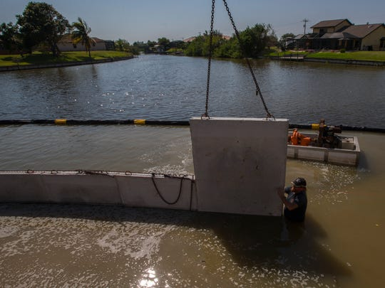 Bubba Williamson, of Williamson & Sons Marine Construction, positions a concrete panel during the assembly process of a seawall for a new Cape Coral home Monday afternoon, 9/18/17.