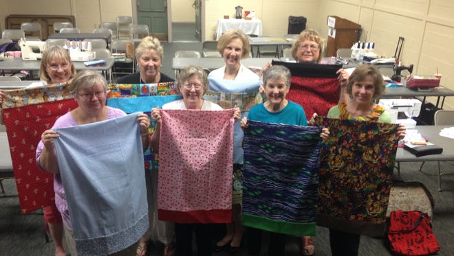 The group poses with their finished pillowcases.