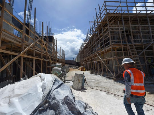 A BME & Sons, Inc. construction worker walks through the Alegria Townhouse Project building site in Tumon in this March 14, 2017, file photo. Company owner Bernie Maranan said he would lose 60 percent of his workers that month because of visa restrictions, making it unclear when the project would be completed.