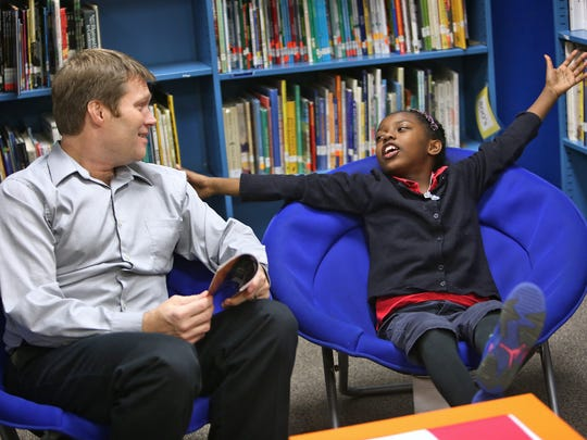 Ka'Leea Johnson (right) tells volunteer Alan Witchey what kind of store she would have at the Mall of America, as they read about it together at IPS School #56 during the ReadUP program, on December 4, 2014.