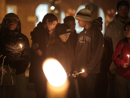Mourners gather at a candlelight vigil on Tuesday,