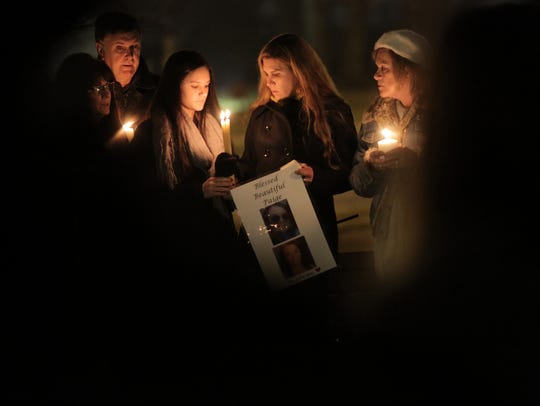 Mourners gather at a candlelight vigil Dec. 23, 2014,