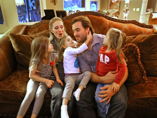 Ben Utecht gets kisses from his daughters — Elleora, Amy Joan and Katriel — and wife, Karyn, in their Lakeville, Minn., home, Wednesday, Nov. 12, 2014.
