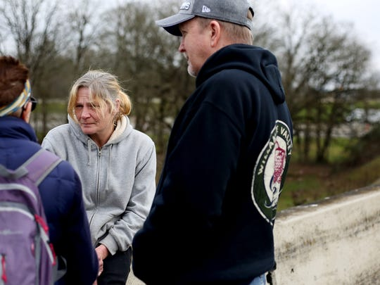 Volunteers Pamela Watson (left) and Jerry Stevens (right) speak with and survey Cindy Honeycutt, 46, (center) about her life as a homeless woman near Highway 22 and I-5 in Salem on Wednesday, Jan. 28, 2015.