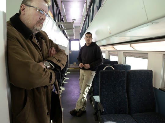 Tim Hoeffner, MDOT Director Office of Rail, left, answers questions as Tim Huffman, senior electrical foreman for Great Lakes Central Railroad stands at right, on a refurbished 1950's era rail car.