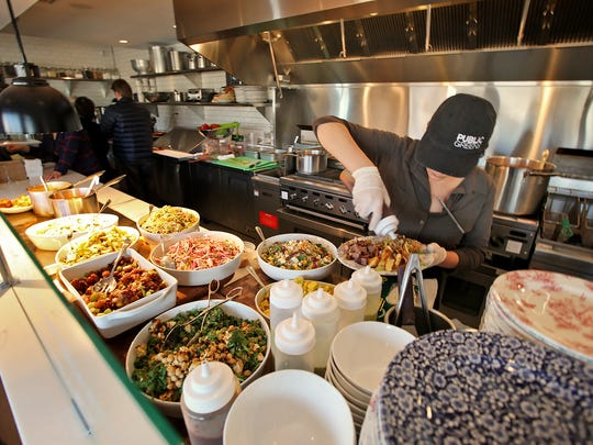 Line cook Shelby Nefouse dishes up food at Public Greens in Broad Ripple, Tuesday, February 3, 2015.