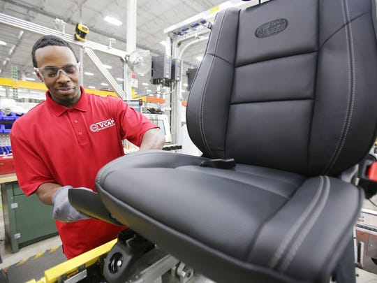 At Magna International, a seat manufacturing company, Stevan Ware, 21, of Detroit repairs Durango Overland seats.