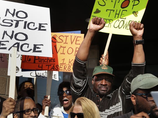 Detroit resident Floyd Dent, 57, raises his arms while
