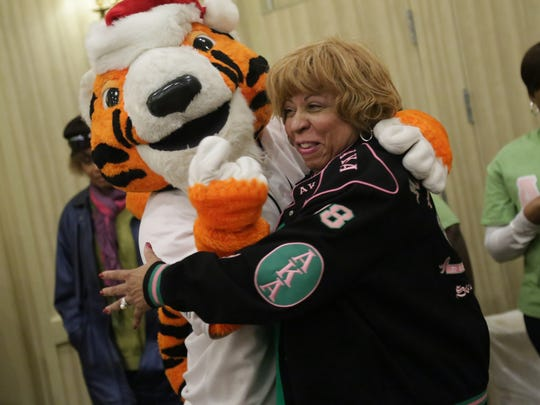 Tigers mascot Paws hugs Tau Alpha Omega chapter president