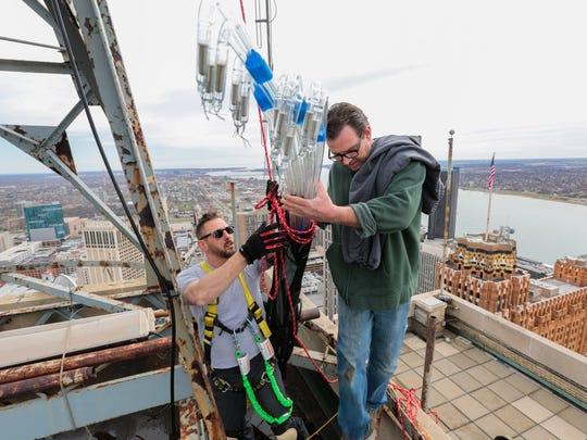 Joe Nelson, right of Roseville helps Todd Farnum of Green Light Detroit load neon tubes into a quiver-like case to hoist up to the ball on the Penobscot Building in downtown Detroit on Tuesday. Later, they used a pulley to raise the tubes which cost about $50 each.