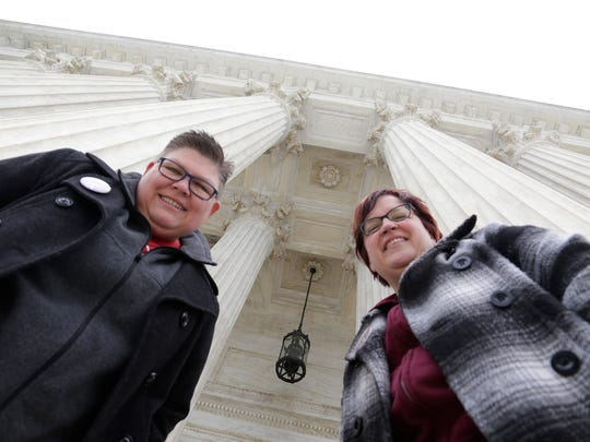 Jayne Rowse, 50, left, and April DeBoer, 44, right, stand under the pillars of the U.S. Supreme Court in Washington D.C. Saturday Apr. 25, 2015.