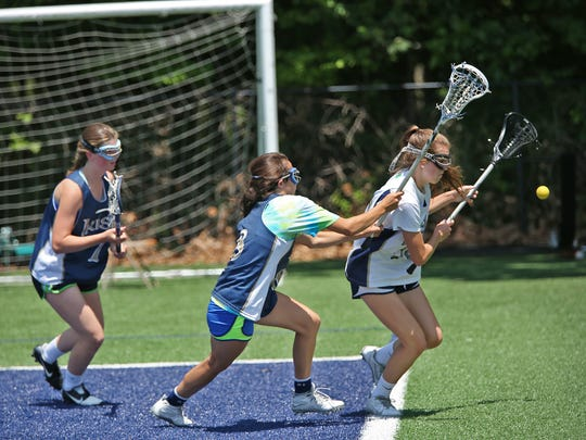 Emily Howard, from left, Kate Burnside, and Taylor Trieloff head for the ball during lacrosse practice at Cathedral High School, Thursday, May 28, 2015.