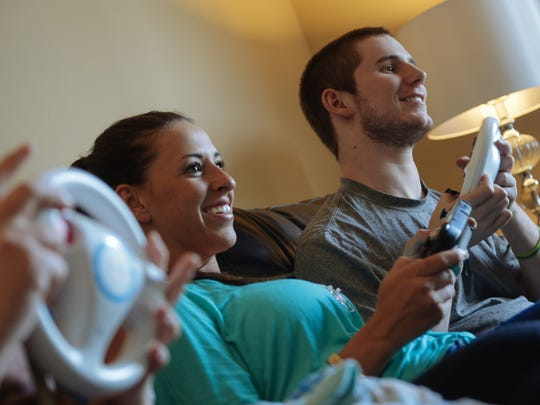 Chris Norton plays Wii with his fiancee Emily Summers